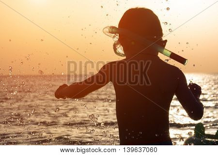 little kid with a mask and snorkel on a background of splashing and sea sunset