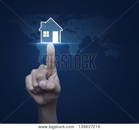 Hand pressing house icon with copy space over digital world map blue background Real estate concept Elements of this image furnished by NASA