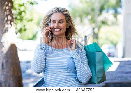 Happy woman talking on cellphone while holding shopping bags at street