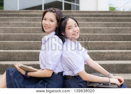 Cute Asian Thai high schoolgirls student couple in school uniform sitting and leaning on her friend's back on the stairway with a sweet happy smiling face on a building stairs