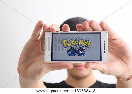 Kuala Lumpur,Malaysia 23th July 2016,teenager holding a smartphone with pokemon go logo on the screen