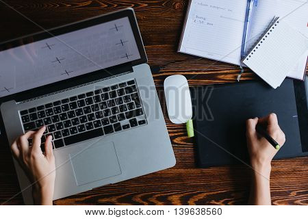 Young female designer working on computer. top view