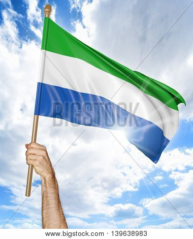 Person's hand holding the Sierra Leone national flag and waving it in the sky, 3D rendering