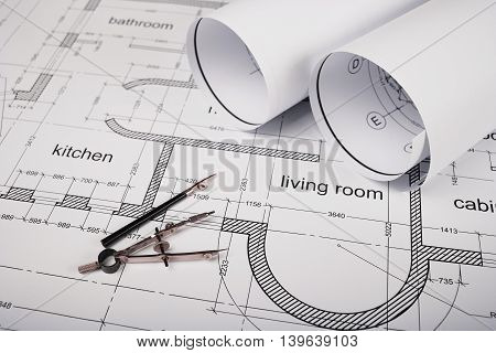 Construction of the building layout, building drawing on paper, a set of drawing tools, blueprints rolled up into a roll.