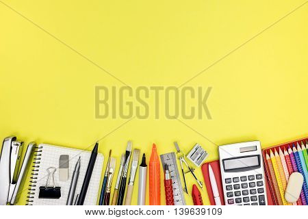 Variety Of School Stationary And Accessories For Education On Yellow Table