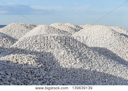 High mounds of white crushed stone on a background of blue sky