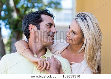 Close-up of romantic couple embracing by building
