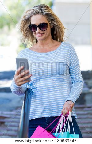 Pretty woman using cellphone while carrying shopping bags on street