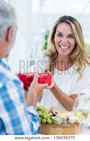 Portrait of happy mature woman receiving gift from husband in restaurant