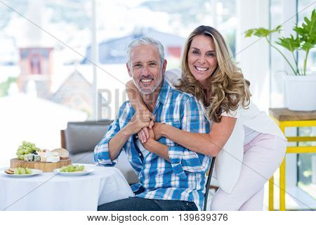 Portrait of cheerful woman embracing husband by table in restaurant