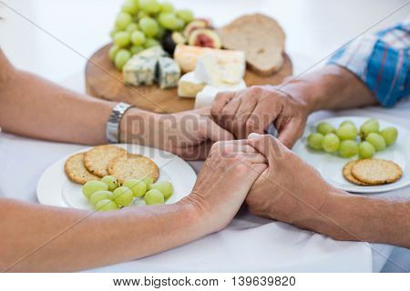 Cropped image of couple holding hands while having food at restaurant