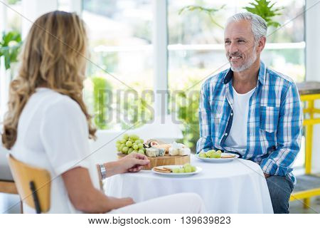 Happy mature couple sitting in restaurant