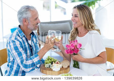 Happy mature couple toasting wineglass at table in restaurant