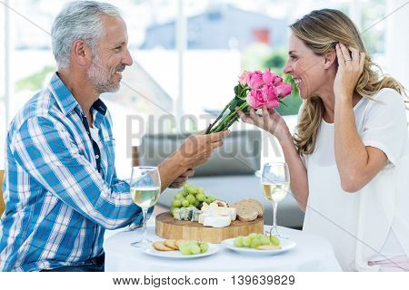 Side view of happy mature man giving pink roses to wife while sitting in restaurant