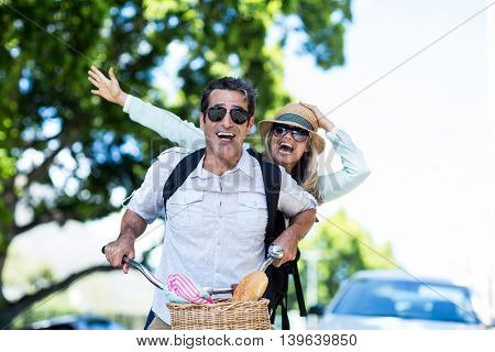 Cheerful mid adult couple riding bicycle at street on sunny day
