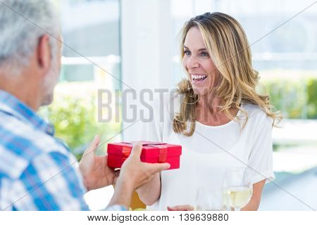 Man giving gift box to happy wife in restaurant