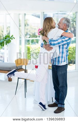 Full length of happy woman embracing husband at restaurant