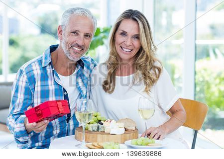 Portrait of happy mature man holding gift while sitting beside wife in restaurant