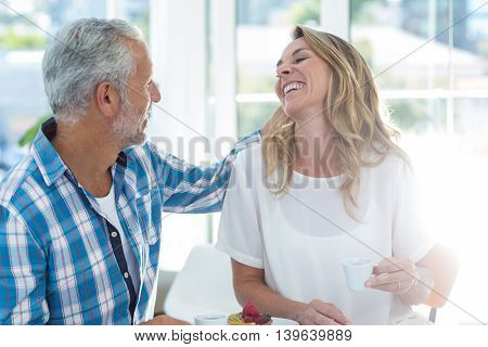 Happy mature couple having coffee in restaurant