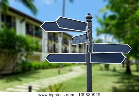 Blank sign label on a pole on blurred hotel resort background with clipping path.