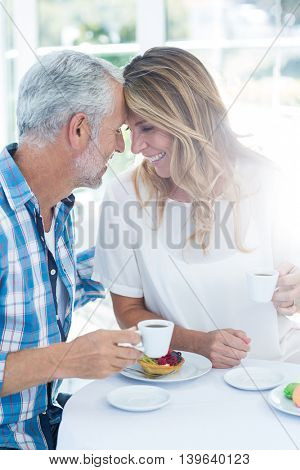 Happy romantic mature couple holding coffee cup at table in restaurant