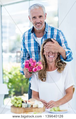 Man covering eyes of wife while giving pink roses in restaurant