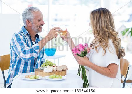 Cheerful mature couple toasting wineglass at table in restaurant