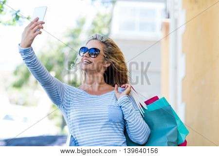 Beautiful woman taking selfie while carrying shopping bags on street in city
