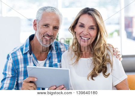 Portrait of happy mature couple holding digital tablet in restaurant