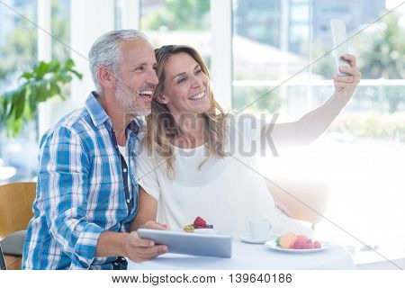 Happy mature couple taking selfie by table in restaurant