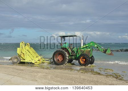 ST LUCIA CARIBBEAN 17 January 2015: Surf rake on tractor by sea