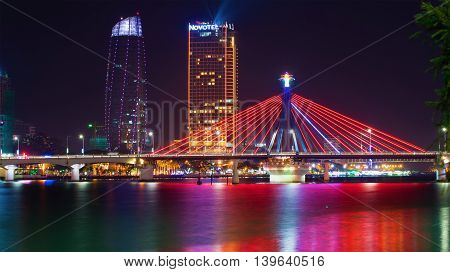 DA NANG, VIETNAM - JANUARY 06, 2016: The South bridge on the background of the modern Novotel Danang Premier Han River. Night in Da Nang, Tourist landmark