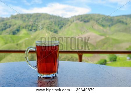 A glass of hot tea on table in tea shop with tea plantations background at Cameron Highlands Malaysia.