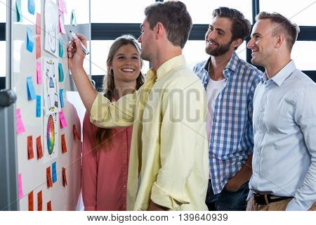 Businessman writing on whiteboard while discussing with colleagues in creative office