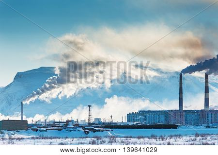 Smokestacks polluting the air over the city. Winter landscape.