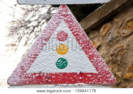 traffic sign in snow with warning of traffic light