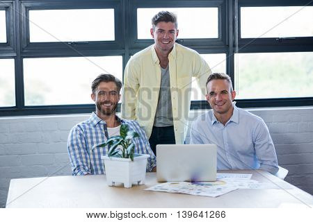 Portrait of smart creative businessmen by table in office