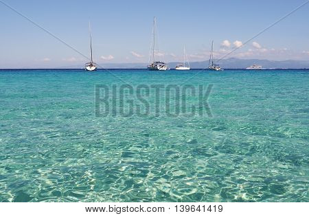 Turquoise sea and sailing boats on the horizon. Greece