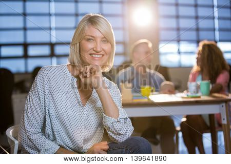 Portrait of smiling creative businesswoman with hand on chin sitting on chair at office