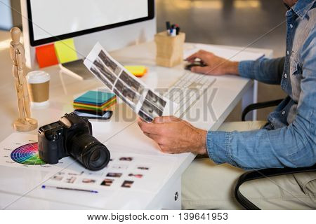 Midsection of photo editor working at computer desk in creative office