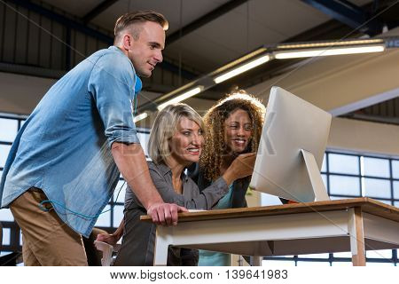 Low angle view of happy business people discussing over computer at desk in creative office