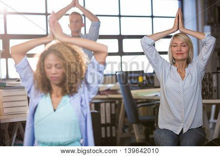 Businesswoman practicing yoga with colleagues in creative office