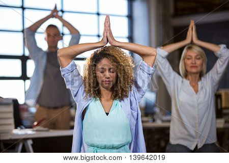 Business people practicing yoga in creative office