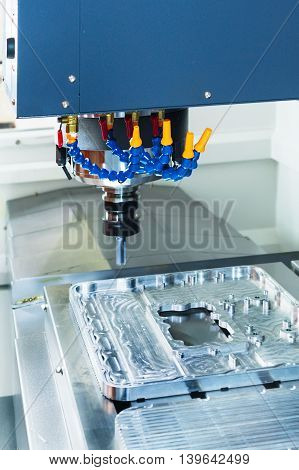 CNC milling machine during operation. Produce drill holes in the aluminium detail.