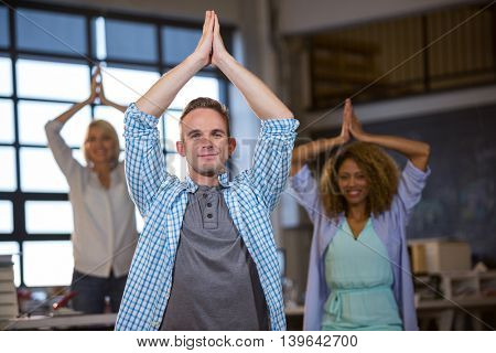 Business people smiling while practicing yoga in creative office