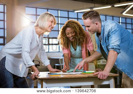 Creative business people smiling discussing over documents at desk in office