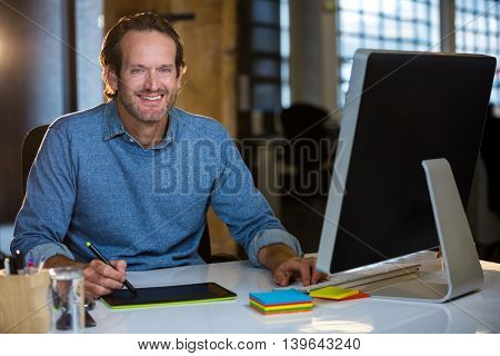 Portrait of confident photo editor working at desk in creative office