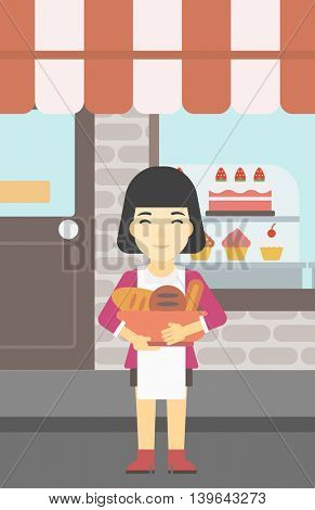 An asian  young female baker holding basket with bakery products. Female baker standing in front of bakery. Baker with bowl full of bread. Vector flat design illustration. Vertical layout.