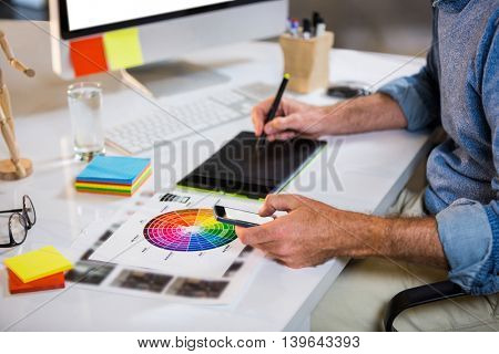 Midsection of businessman using graphics tablet at desk in creative office