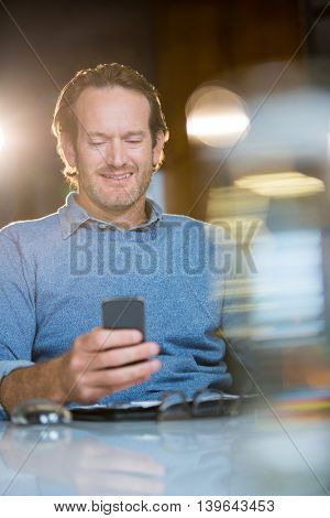 Creative businessman using mobile phone at desk in office